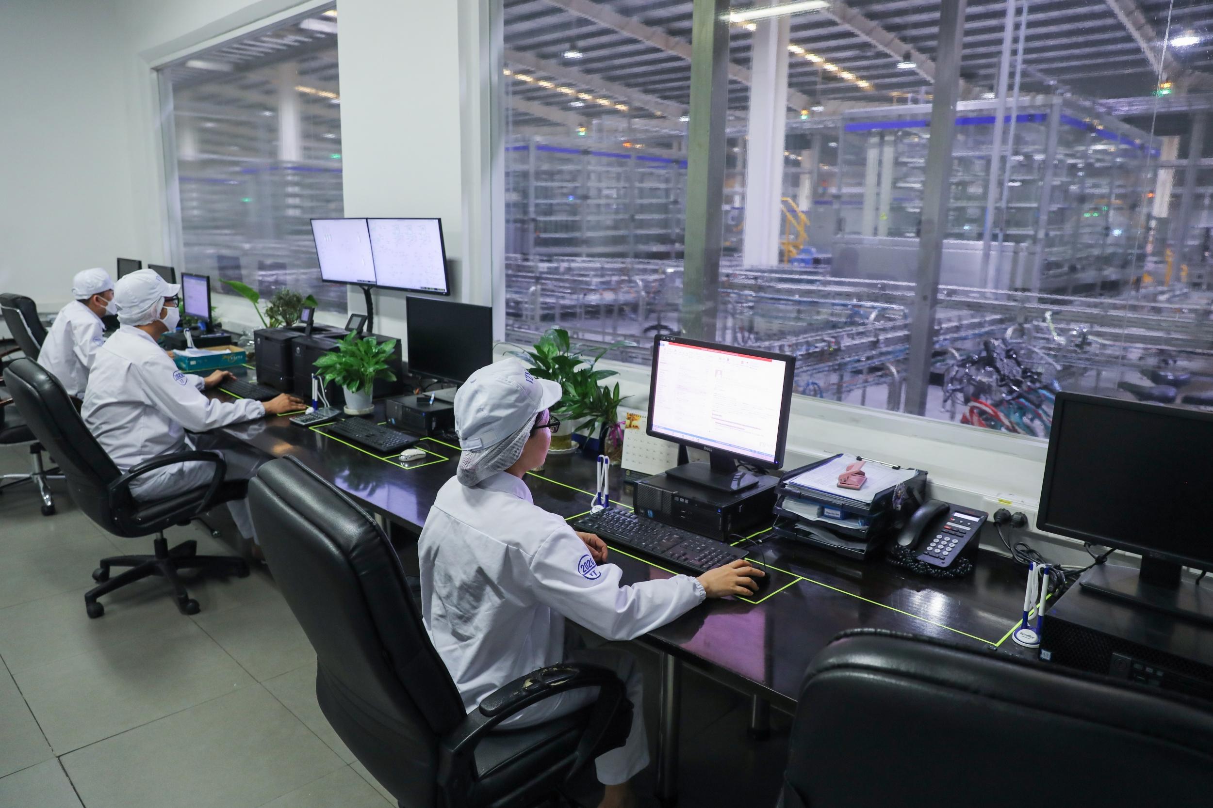 Các nhân viên tại nhà máy Vinamilk ở Bình Dương đang vận hành dây chuyền sản xuất sữa hiện đại hoàn toàn tự động hóa qua hệ thống máy tính.