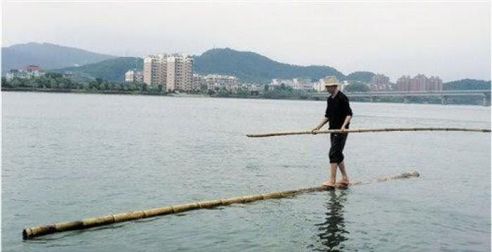 Người đàn ông lướt đi trên sông chỉ với một cây tre