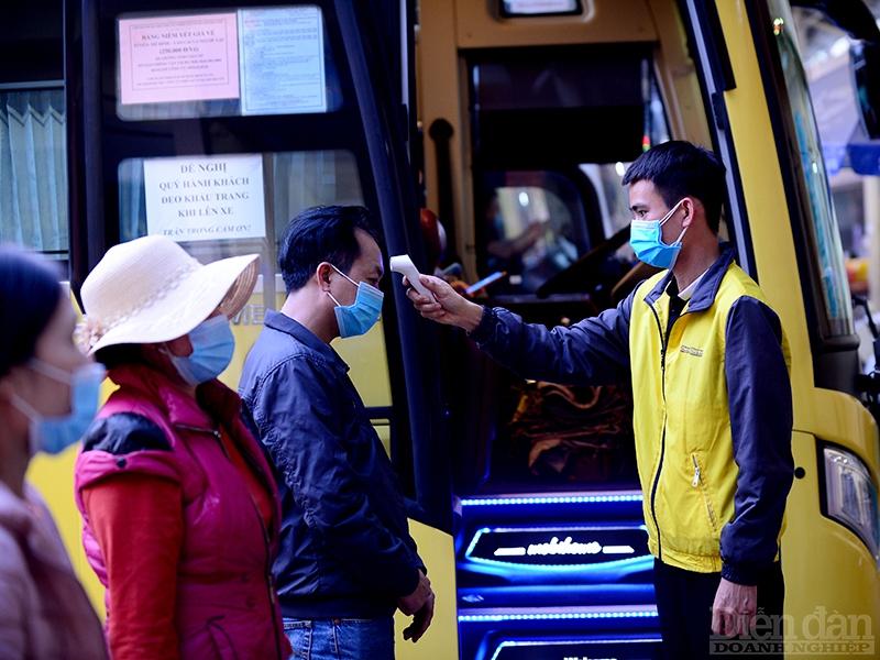 Hành khách được đo thân nhiệt trước khi lên xe.