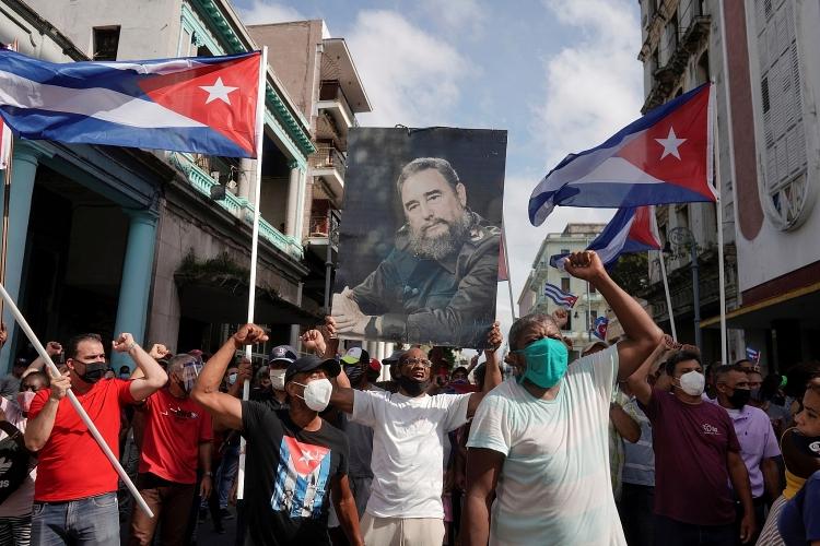 Người ủng hộ chính phủ Cuba cầm ảnh cố Chủ tịch Fidel Castro xuống đường ở Havana vào ngày 11.7.
