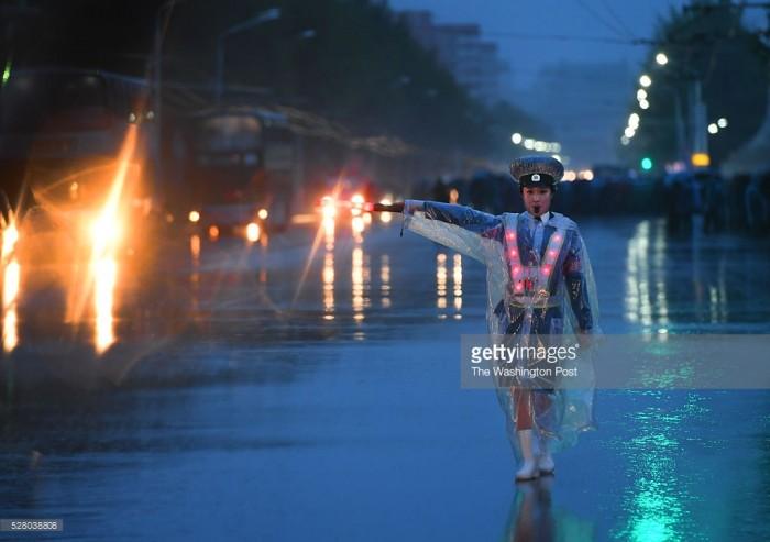 Một nữ cảnh sát chỉ huy giao thông trong cơn mưa tầm tã ở Bình Nhưỡng ngày 3/5